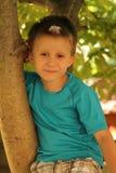 Uśmiechnięta chłopiec na drzewie Obraz Stock