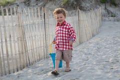 Uśmiechnięta chłopiec na plaży z Błękitnym Pail przy zmierzchem Obrazy Stock