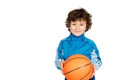 Uśmiechnięta chłopiec patrzeje kamerę z koszykową piłką Obrazy Royalty Free