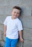 Uśmiechnięta chłopiec patrzeje kamerę z niebieskimi oczami Zdjęcie Stock