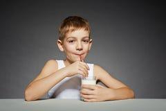 Uśmiechnięta chłopiec pije mleko Obrazy Royalty Free