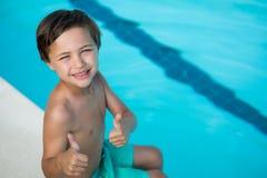 Uśmiechnięta chłopiec pokazuje aprobaty przy poolside Zdjęcie Royalty Free