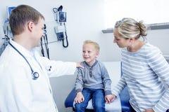Uśmiechnięta chłopiec przy lekarki biurem Fotografia Stock