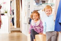 Uśmiechnięta chłopiec robiąca zakupy i dziewczyna jesteśmy wpólnie podczas gdy Zdjęcia Stock