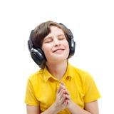 Uśmiechnięta chłopiec słucha muzykę w hełmofonach Obrazy Royalty Free