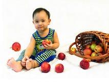 Uśmiechnięta chłopiec siedzi z koszem jabłka obrazy royalty free