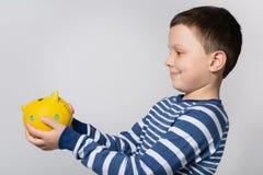 Uśmiechnięta chłopiec trzyma żółtego prosiątko banka przed on, patrzejący prosiątko banka, pojęcie oszczędzania zdjęcia stock