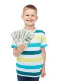 Uśmiechnięta chłopiec trzyma dolara gotówkowego pieniądze w jego ręce Obraz Stock