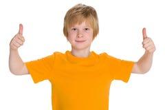 Uśmiechnięta chłopiec trzyma jego aprobaty obraz stock