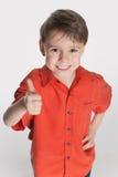 Uśmiechnięta chłopiec trzyma jego kciuk up obrazy royalty free