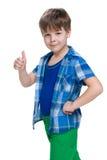 Uśmiechnięta chłopiec trzyma jego kciuk up Zdjęcie Royalty Free