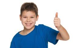 Uśmiechnięta chłopiec trzyma jego kciuk up w błękitnej koszula zdjęcia stock