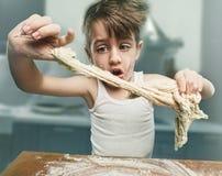 Uśmiechnięta chłopiec ugniata ciasto zdjęcie stock