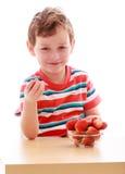 Uśmiechnięta chłopiec w pasiastym koszulki łasowaniu Fotografia Stock
