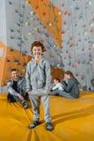 Uśmiechnięta chłopiec w sportive ubiór pozyci przed wspinaczkowymi patrzeć i ścianą obraz stock