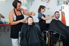 Uśmiechnięta chłopiec w szkoły podstawowej pełnoletniej dostaje fryzurze obraz stock