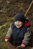 Uśmiechnięta chłopiec wspinał się w kosz z owoc fotografia royalty free