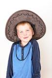 Uśmiechnięta chłopiec z błękitną koszula i wielkim brown kapeluszem Obrazy Royalty Free