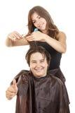 Uśmiechnięta chłopiec z długie włosy z kciukiem up przy fryzjerem Fotografia Royalty Free