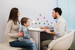 Uśmiechnięta chłopiec z jego matką przy lekarki biurem obraz stock