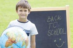 Uśmiechnięta chłopiec z kulą ziemską przeciw blackboard Edukacja Z powrotem szkoły pojęcie Fotografia Royalty Free