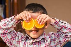 Uśmiechnięta chłopiec z pomarańczami fotografia stock