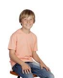Uśmiechnięta chłopiec z pomarańczowym koszulki obsiadaniem Zdjęcia Stock