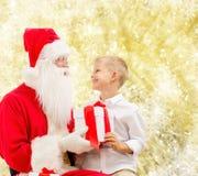 Uśmiechnięta chłopiec z Santa Claus i prezenty Fotografia Royalty Free