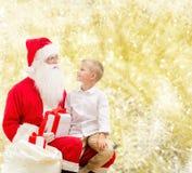 Uśmiechnięta chłopiec z Santa Claus i prezenty Obrazy Royalty Free