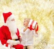 Uśmiechnięta chłopiec z Santa Claus i prezenty Zdjęcie Royalty Free