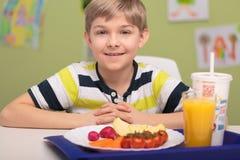 Uśmiechnięta chłopiec z szkolnym lunchem Zdjęcia Stock