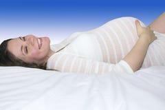 Uśmiechnięta ciężarna matka w bielu paskuje łgarskiego puszek Fotografia Stock
