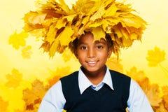 Uśmiechnięta czarna chłopiec jest ubranym liść klonowy koronę Fotografia Royalty Free