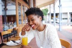 Uśmiechnięta czarna dziewczyna pije sok pomarańczowego przy plenerową kawiarnią Zdjęcia Stock