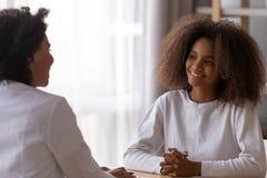 Uśmiechnięta czarna nastoletniej dziewczyny rozmowa z żeńskim obsiadaniem przy stołem obrazy royalty free