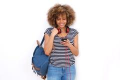 Uśmiechnięta czarny afrykanin kobieta z telefonem komórkowym i torbą przeciw białemu tłu Obrazy Stock