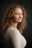 Uśmiechnięta czarodziejska kobieta z czerwonym kędzierzawym włosy, duża pierś na zmroku popielatym Fotografia Stock