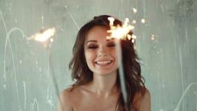 Uśmiechnięta dama w czarnej sukni z sparklers w ręce młoda kobieta ma zabawę i świętować swobodny ruch zdjęcie wideo