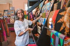 Uśmiechnięta dojrzała kobieta patrzeje kolorową tkaninę w jej sklepie Fotografia Stock