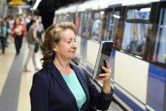 Uśmiechnięta dojrzała kobieta używa eBook w metrze przy stacją metru podczas gdy czekający pociąg Obrazy Stock