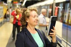 Uśmiechnięta dojrzała kobieta używa eBook w metrze przy stacją metru podczas gdy czekający pociąg Fotografia Stock