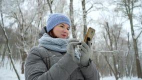 Uśmiechnięta dorosła kobieta bierze selfie na telefonie w zima parku zdjęcie wideo