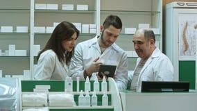 Uśmiechnięta drużyna farmaceuty, dwa męskiego i jeden kobiety, stojak strona popiera kogoś w aptece sprawdza informację na a - ob Obraz Royalty Free