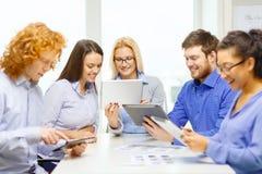 Uśmiechnięta drużyna z stołowym komputerem osobistym i papierów pracować Zdjęcia Stock