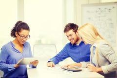 Uśmiechnięta drużyna z stołowym komputerem osobistym i papierów pracować Obrazy Stock