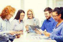 Uśmiechnięta drużyna z stołowym komputerem osobistym i papierów pracować Fotografia Royalty Free