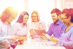 Uśmiechnięta drużyna z stołowym komputerem osobistym i papierów pracować Zdjęcia Royalty Free
