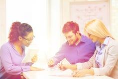 Uśmiechnięta drużyna z stołowym komputerem osobistym i papierów pracować Fotografia Stock