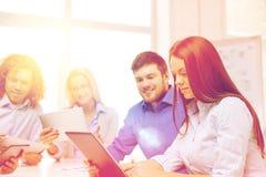 Uśmiechnięta drużyna z stołowym komputerem osobistym i papierów pracować Obrazy Royalty Free