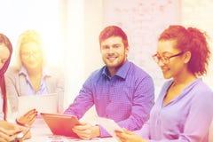 Uśmiechnięta drużyna z stołowym komputerem osobistym i papierów pracować Zdjęcie Royalty Free